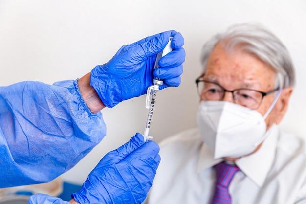 Oudere man kijkt toe terwijl verpleegster in beschermend pak en maandverband zijn vaccin tegen coronavirus klaarmaakt