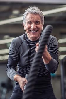 Oudere man lacht tijdens het trainen met touwen in de sportschool, met een koptelefoon op.