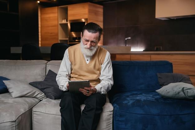 Oudere man leert tablet-computer. elektronische gadgets voor senioren. een man met een stijlvolle baard met behulp van tablet voor surfen op het web.