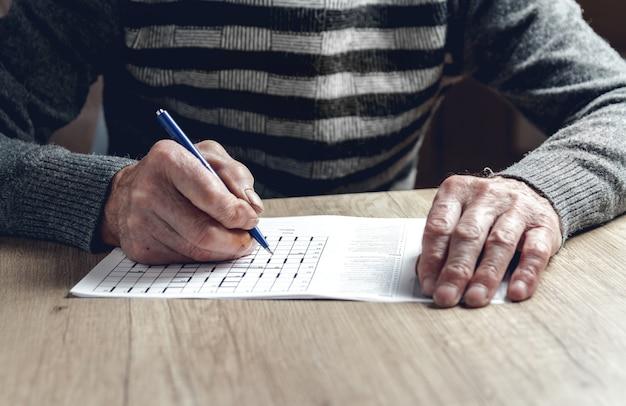 Oudere man lost sudoku of een kruiswoordpuzzel op