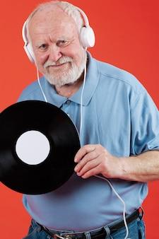 Oudere man luisteren muziek op heaphones