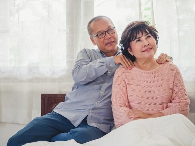 Oudere man masseert de schouders voor de oude vrouw