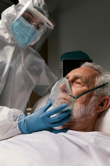 Oudere man met beademingsapparaat in een ziekenhuisbed
