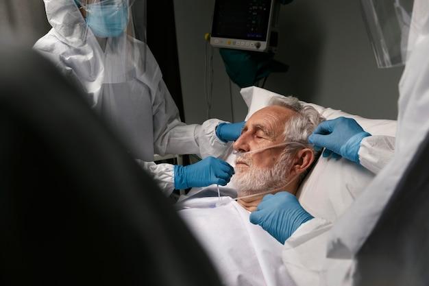Oudere man met beademingsapparaat naast artsen