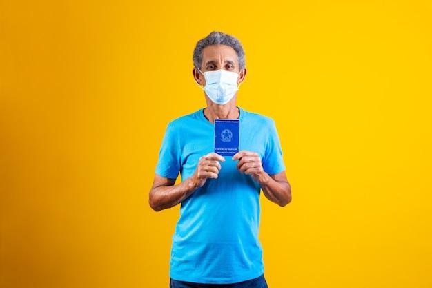 Oudere man met braziliaanse werkkaart in handen en met chirurgisch masker op zijn gezicht. concept van werk in de pandemie