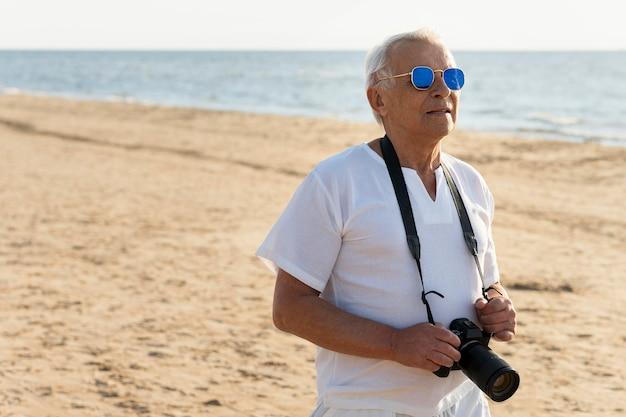 Oudere man met camera aan het strand