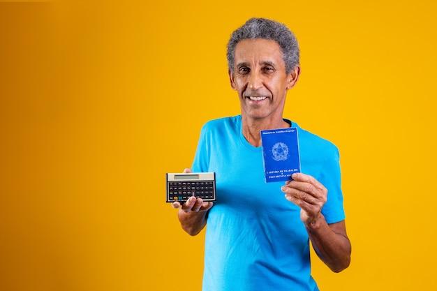 Oudere man met een braziliaanse werkkaart en een rekenmachine