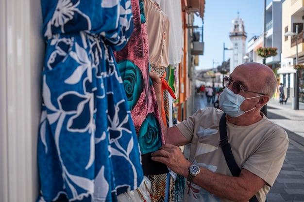 Oudere man met een geschoren hoofd draagt een medisch masker vanwege het coronavirus en kijkt naar de kleding die buiten de winkel wordt getoond - concept van oudere gepensioneerde tijdens het winkelen