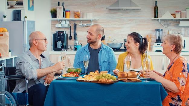 Oudere man met een handicap met goed nieuws voor zijn gezin. oudere senior in rolstoel glimlachen, wijn drinken en eten tijdens een gastronomische maaltijd, genietend van ontspannende tijd.