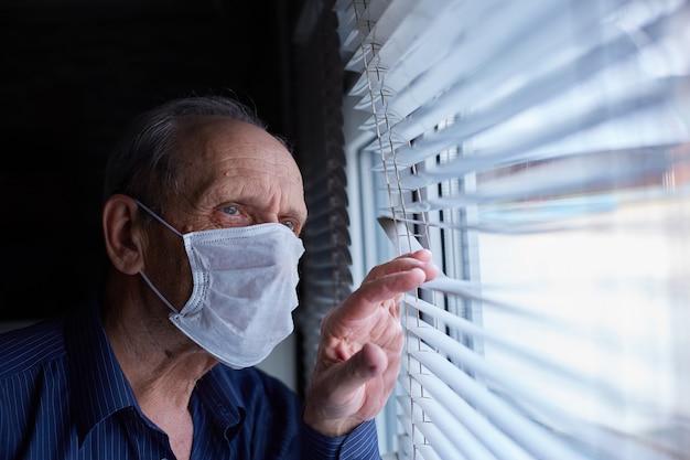 Oudere man met een medisch masker is in quarantaine en in zichzelf geïsoleerd