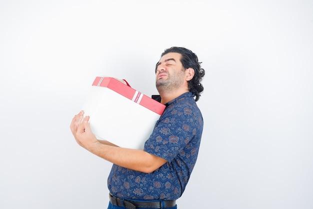 Oudere man met geschenkdoos in shirt en op zoek moe, vooraanzicht.