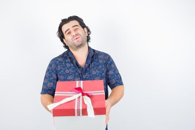 Oudere man met geschenkdoos in shirt en op zoek schattig, vooraanzicht.