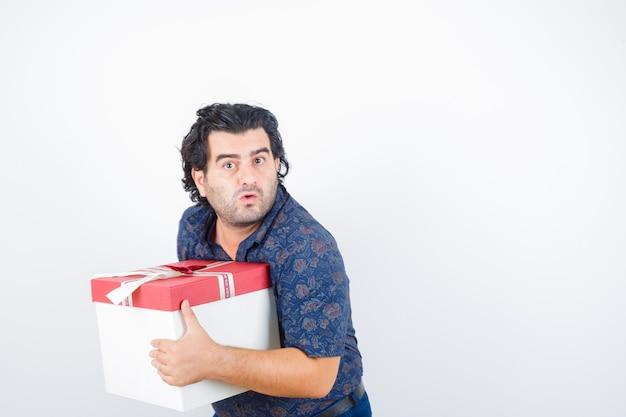 Oudere man met geschenkdoos in shirt en op zoek verbaasd, vooraanzicht.