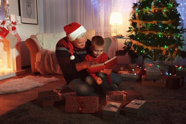 Oudere man met kleinzoon leesboek in woonkamer ingericht voor kerstmis