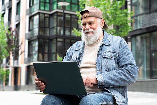 Oudere man met laptop buiten in de stad