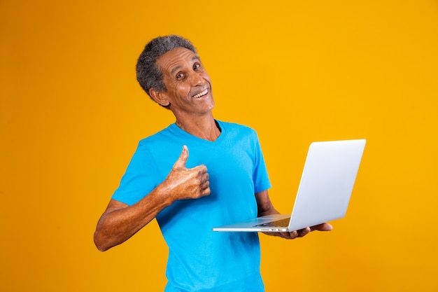 Oudere man met laptop die online winkelt of werkt. oudere man met zijn duim omhoog met een notebookcomputer.