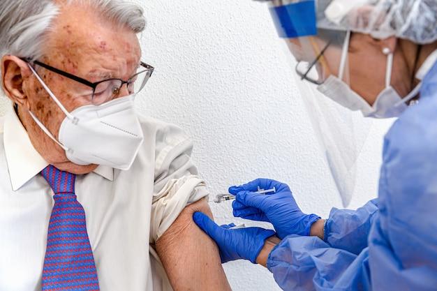 Oudere man met masker kijkt toe terwijl verpleegster in beschermend pak en covid-masker hem het coronavirusvaccin geeft