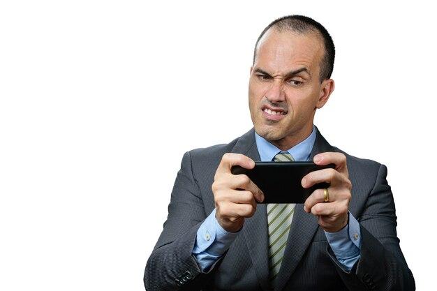 Oudere man met pak en stropdas, spelen op zijn smartphone en een grappig boos gezicht maken.