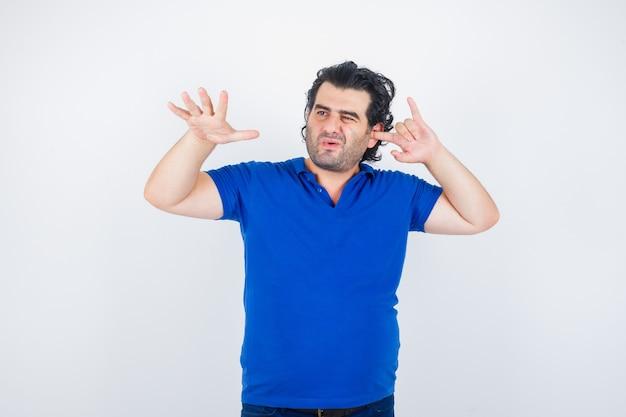 Oudere man met stop gebaar, oor met vinger in blauw t-shirt inpluggen en op zoek verveeld. vooraanzicht.