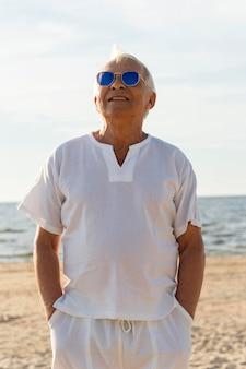 Oudere man met zonnebril aan het strand