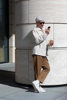 Oudere man met zonnebril buiten in de stad die smartphone gebruikt terwijl hij koffie drinkt