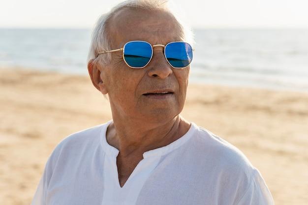 Oudere man met zonnebril genieten van zijn tijd op het strand