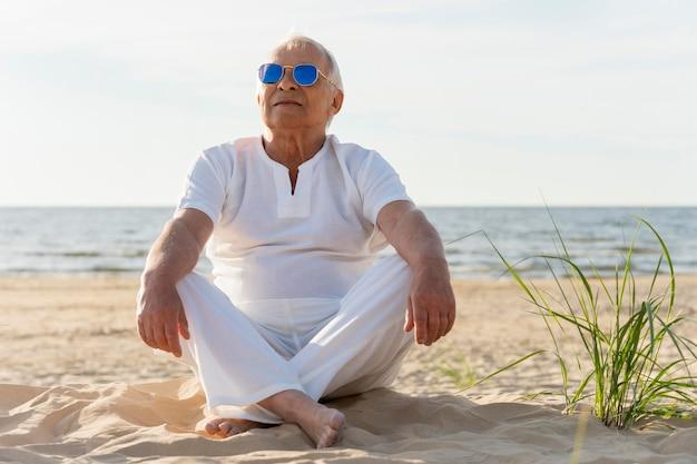Oudere man met zonnebril op het strand