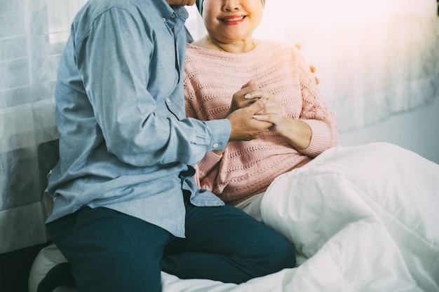 Oudere man moedigt zijn vrouw aan tijdens chemotherapie om kanker te genezen.