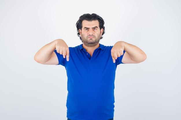 Oudere man naar beneden met wijsvingers in blauw t-shirt, op zoek boos, vooraanzicht.