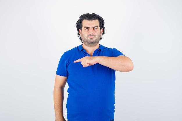 Oudere man naar links wijzend met wijsvinger in blauw t-shirt, boos kijkt. vooraanzicht.