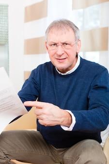 Oudere man of senior hebben een brief ontvangen, misschien is het een herinnering of een rekening