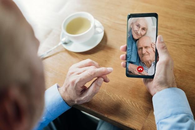 Oudere man praat met zijn vrienden via een videogesprek