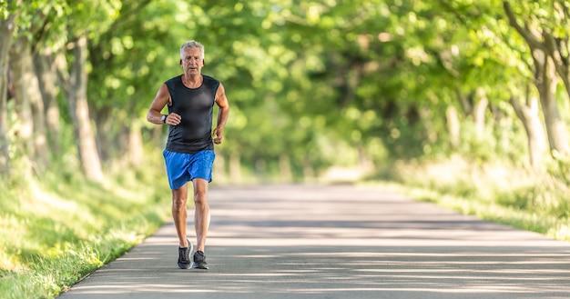 Oudere man rent bergopwaarts in de natuur tijdens een zomerdag en houdt zijn conditie hoog.