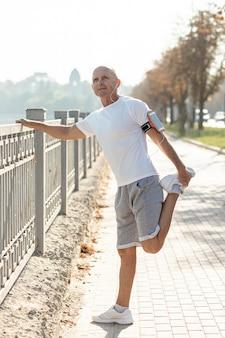 Oudere man runner die zich uitstrekt