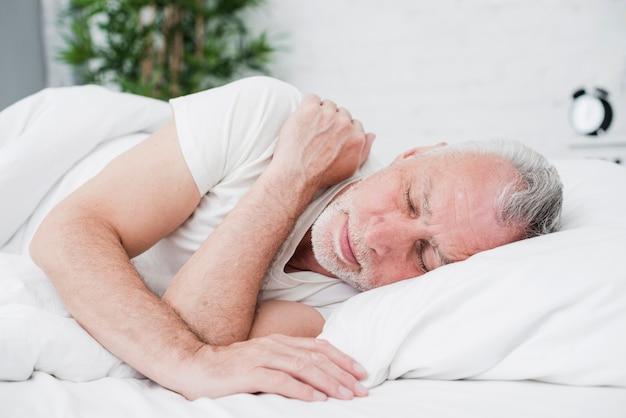 Oudere man slaapt in een witte bed