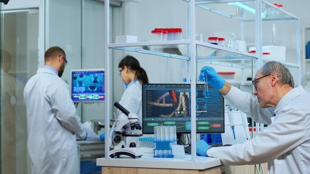 Oudere man technoloog doet een laboratoriumtest die een kolf met een blauwe substantie onderzoekt, een scheikundige buis met vloeistoffen erin. wetenschapper die werkt met verschillende bacterieweefsel- en bloedmonsters