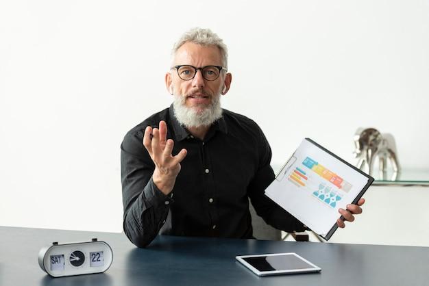 Oudere man thuis met grafiek op notitieblok met tablet op bureau