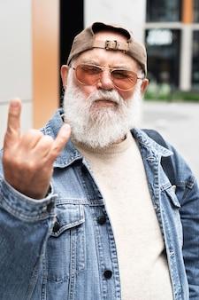 Oudere man toont rock-'n-roll-gebaar buiten in de stad
