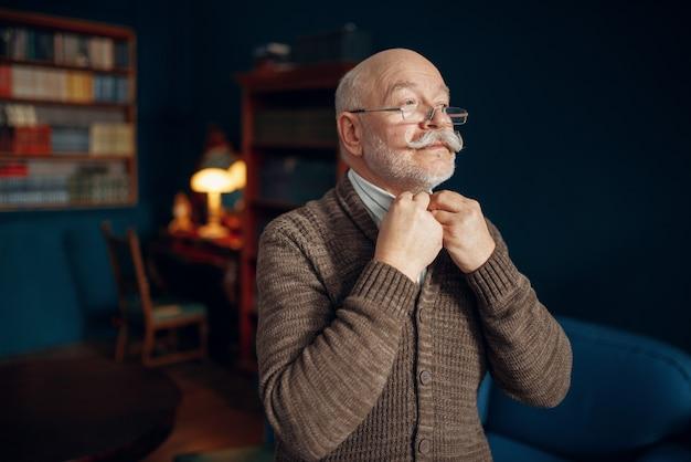 Oudere man trekt een gelijkspel in kantoor aan huis