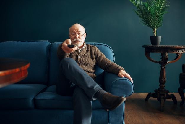 Oudere man tv kijken op de bank in kantoor aan huis. bebaarde volwassen senior vormt in de woonkamer, ouderdomszakenman