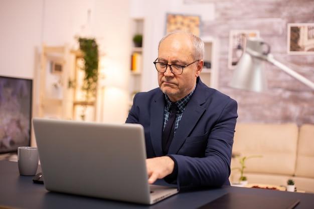 Oudere man typen op laptop in gezellige woonkamer.