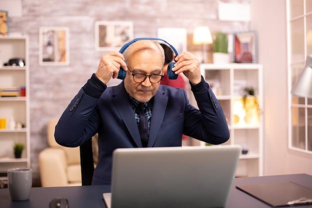 Oudere man van in de 60 met koptelefoon op zijn hoofd die naar muziek luistert en op een moderne laptop werkt
