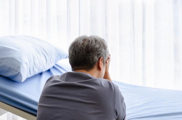 Oudere man voelt verdriet lijden op bed van patiënt voor overleden vrouw in ziekenhuis