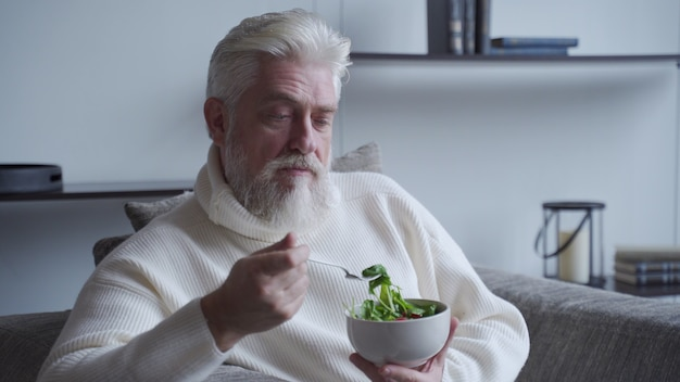 Oudere man voelt zich gelukkig geniet van het eten van verse salade van dieetvoedsel op de bank