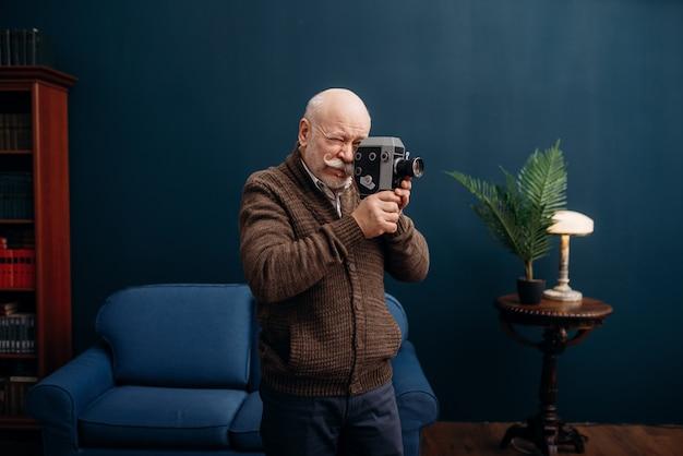 Oudere man vormt met oude filmcamera in kantoor aan huis. bebaarde volwassen senior in de woonkamer, ouderdomszakenman