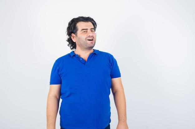 Oudere man wegkijken in blauw t-shirt en op zoek benieuwd, vooraanzicht.