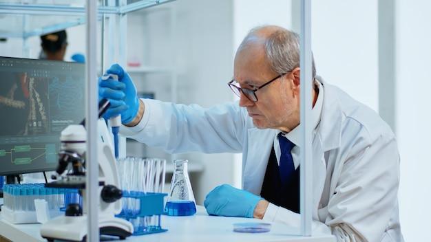 Oudere man wetenschapper met behulp van micropipet voor het vullen van reageerbuizen in modern uitgerust laboratorium. multi-etnisch team onderzoekt virusevolutie met behulp van hightech voor vaccinontwikkeling tegen covid19