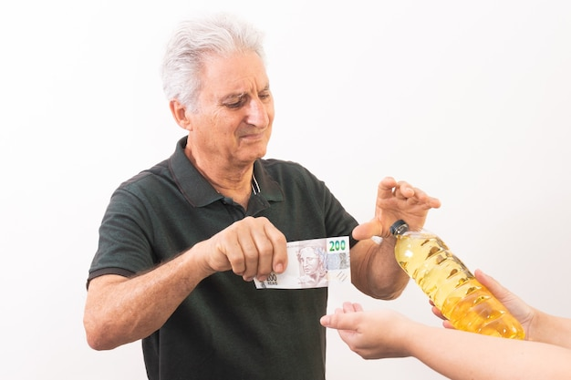 Oudere man wisselt biljet van 200 braziliaanse reais in voor een liter bakolie