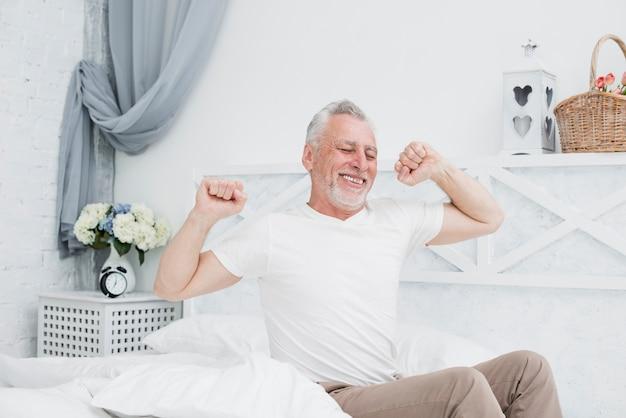 Oudere man wordt wakker in het bed