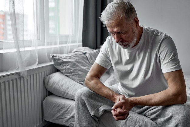 Oudere man zit alleen thuis, sociale afstandelijkheid en zelfisolatie in quarantaine-afsluiting voor coronavirus